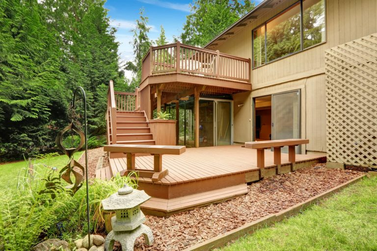 A picture of a large multi level deck with benches in the back yard of a house.