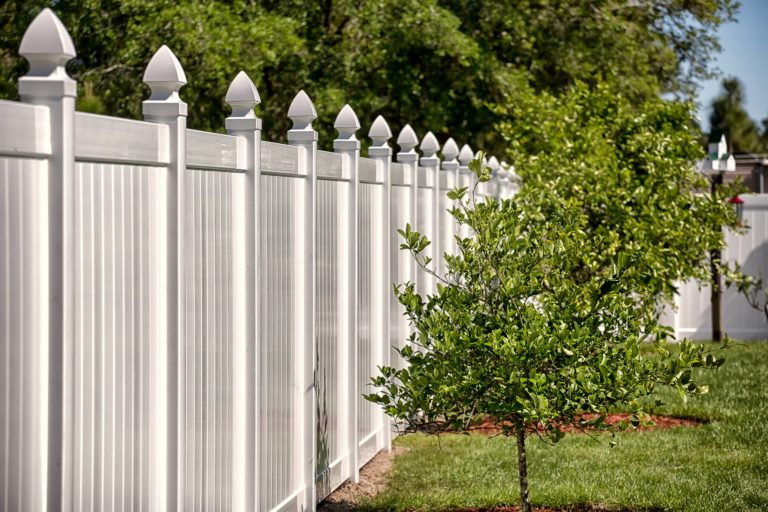 An image of a stylish white fence with pointed posts.