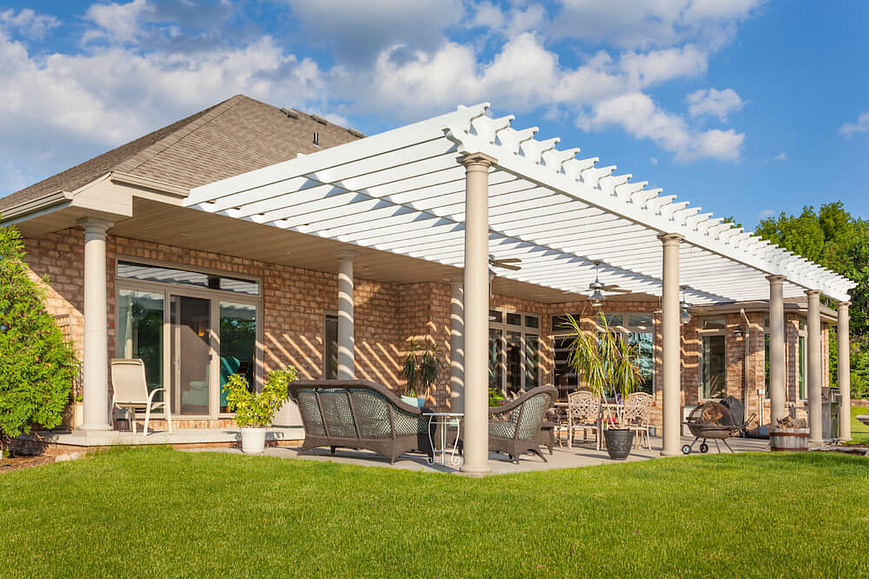 A picture of a luxurious white pergola supported by pillars over a patio seating area for a luxury home.