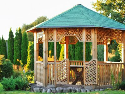 A picture of a beautiful gazebo with bench in a scenic sunny area.