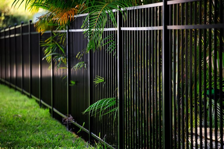 This image is of a tall metal fence surrounding a property.